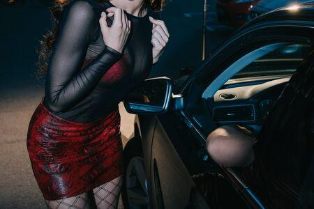 vista ritagliata della donna in gonna rossa in piedi vicino all'uomo in macchina