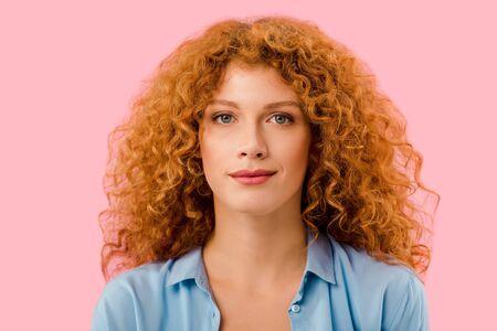 schönes lächelndes rothaariges Mädchen isoliert auf rosa