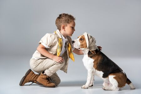 explorer kid with yellow kerchief  and beagle dog in hat on grey