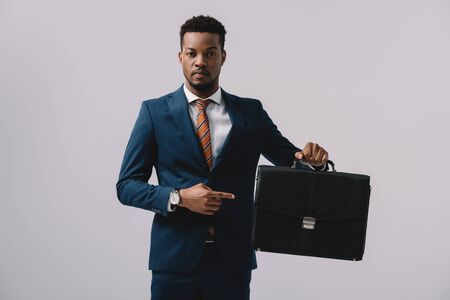 homme afro-américain pointant du doigt sur une mallette isolée sur fond gris