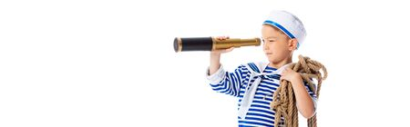 panoramic shot of focused boy in sailor costume holding rope and looking through spyglass isolated on white Banco de Imagens