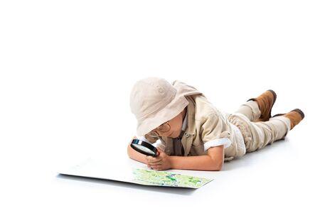 bambino esploratore concentrato in cappello e occhiali guardando la mappa attraverso la lente di ingrandimento su bianco Archivio Fotografico