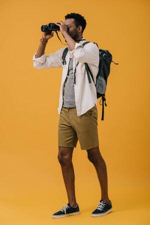 african american man looking through binoculars on orange 免版税图像