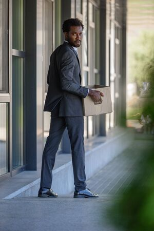 selective focus of fired african american businessman looking back while holding carton box