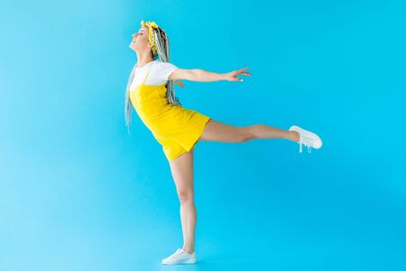 happy girl with dreadlocks with outstretched hands and leg posing on turquoise Stock fotó