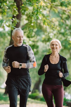 cheerful mature sportsman and sportswoman running together in park