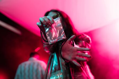 girl holding plastic zipper bag with drugs in nightclub, selective focus
