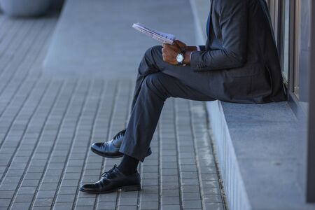 cropped view of african american businessman reading newspaper while sitting on parapet Banque d'images