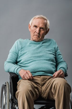 upset senior man sitting in wheelchair and looking at camera isolated on grey