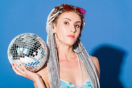 beautiful stylish girl posing with disco ball and looking at camera on blue Banco de Imagens