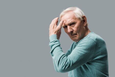exhausted and upset retired man gesturing and looking at camera isolated on grey