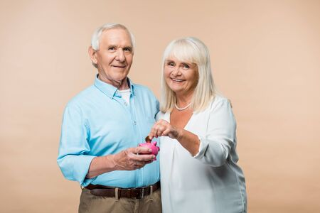 cheerful retired man holding pink piggy bank while senior wife putting coin isolated on beige Standard-Bild