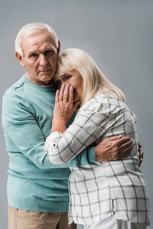 sad retired man hugging frustrated senior wife covering face isolated on grey Stockfoto