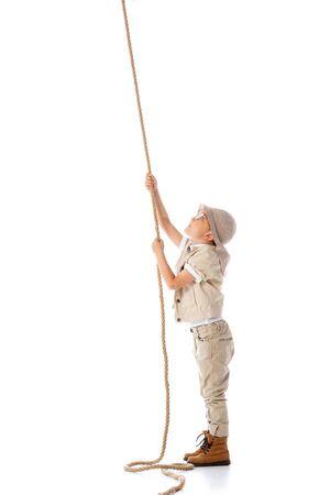 Vue sur toute la longueur de l'enfant explorateur concentré en chapeau et lunettes tenant une corde isolée sur blanc