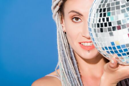 beautiful girl with dreadlocks covering face with disco ball isolated on blue Фото со стока