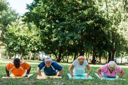 Deportivos jubilados y multiculturales hombres y mujeres haciendo ejercicio en colchonetas de fitness Foto de archivo