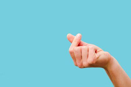Ausgeschnittene Ansicht der weiblichen Hand, die mit den Fingern isoliert auf Blau schnippst Standard-Bild
