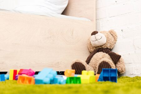 Plush bear and scattered pieces of construction on green carpet near wooden bed Stock Photo