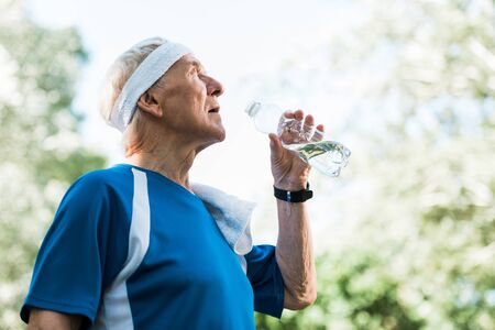 low angle view of senior man holding bottle with water