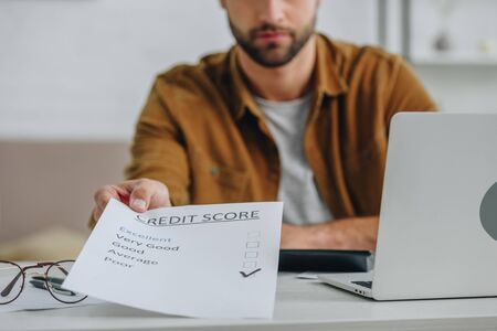 cropped view of man in shirt holding credit score