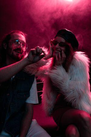 man giving marijuana joint to smiling girl in nightclub