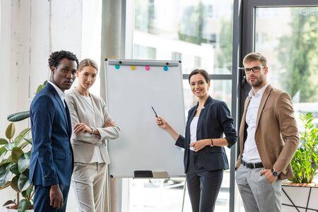 four smiling multiethnic colleagues in formal wear standing near flipchart in office