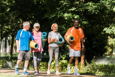 positive retired and multicultural pensioners holding fitness mats and walking in park