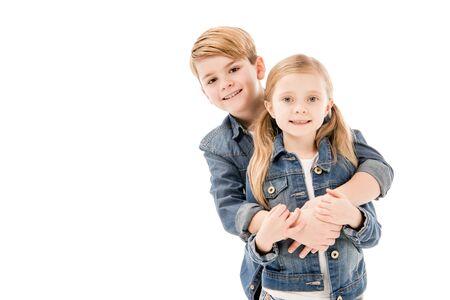 Niños felices abrazándose y mirando a la cámara aislada en blanco Foto de archivo