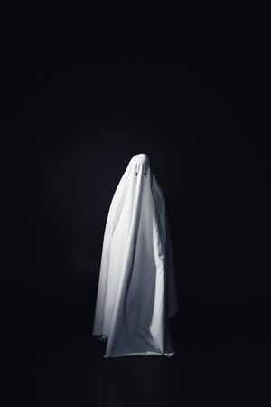 horrible ghost in white bedsheet isolated on black with copy space