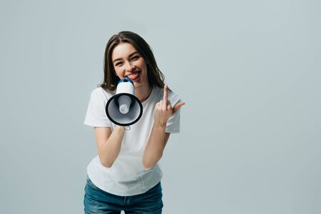 happy young pretty woman with loudspeaker showing middle finger isolated on grey