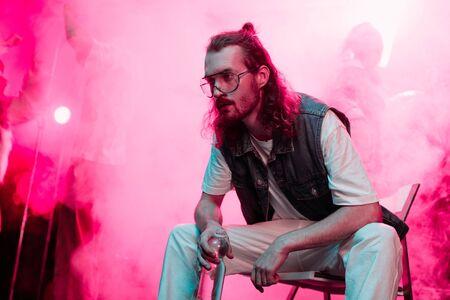 sick man sitting with bottle of water in nightclub