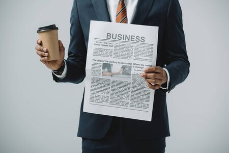 cropped view of african american man holding disposable cup and business newspaper isolated on grey