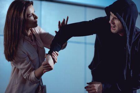 Bella mujer peleando con ladrón en el paso subterráneo Foto de archivo
