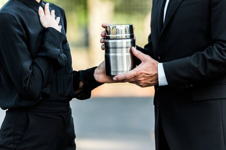cropped view of man and woman holding mortuary urn in graveyard