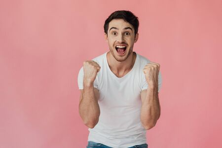 front view of excited muscular man in white t-shirt showing yes gesture isolated on pink 版權商用圖片