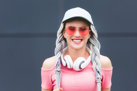 beautiful stylish girl with dreadlocks and headphones smiling and looking at camera Фото со стока