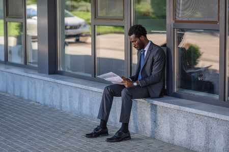 concentrated african american businessman reading newspaper while sitting on parapet of office building
