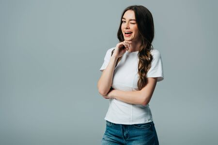 beautiful girl in white t-shirt winking with open mouth isolated on grey Stock Photo