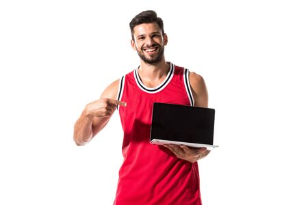 happy athletic basketball player pointing with finger at laptop Isolated On White Reklamní fotografie