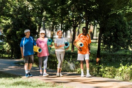 cheerful retired and multicultural pensioners holding fitness mats and walking in park