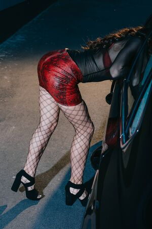 cropped view of prostitute in red skirt and stockings standing near car Stock fotó