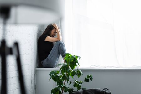 selective focus of depressed young woman crying while sitting on window sill and holding hands on head