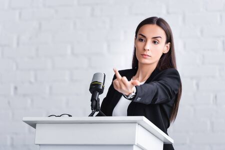 dissatisfied lecturer standing on podium tribune in conference hall and showing middle finger