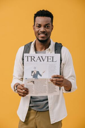 curly african american man standing with backpack and holding travel newspaper isolated on orange 写真素材
