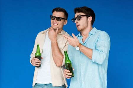 two friends in 3d glasses holding bottles of beer isolated on blue