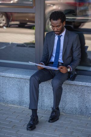 focused african american businessman reading newspaper while sitting near office building