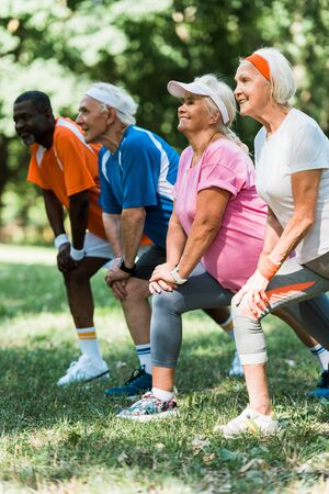 selective focus of cheerful senior and multicultural people doing stretching exercise on grass Foto de archivo - 130213015