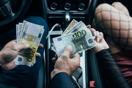 cropped view of prostitute in mesh stockings receiving money from client in car Stock fotó