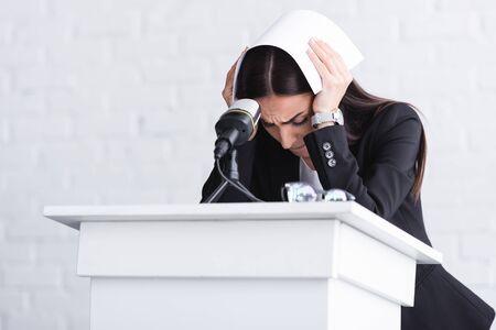 junger Dozent, der unter Angst vor öffentlichen Reden leidet, auf der Tribüne steht und den Kopf mit Papier bedeckt Standard-Bild