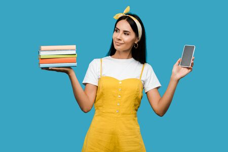young woman holding books and smartphone with blank screen isolated on blue